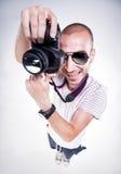 Türspion schoss vom lustigen Fotografen, der mit einem Kameralächeln aufwirft Stockfotos
