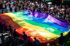 Tęczy flaga niosąca ludźmi zbiera darowizny podczas dumy parady obraz royalty free