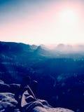 Tęsk męczył męskie nogi w zmroku wycieczkuje spodnia bierze odpoczynek na szczycie skała nad dolina Zdjęcia Royalty Free