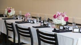 Tęsk stół z białym stołowym płótnem dekorującym dla poślubiać Zdjęcia Stock