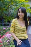 Tęsk z powrotem włosiana azjatykcia dziewczyna w ogródzie Obrazy Stock