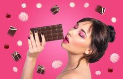 tła czekolady biała kobieta Piękna młoda kobieta je czekoladę Obraz Royalty Free