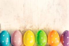 tła kolorowi Easter jajka Biały drewno stół kosmos kopii Obrazy Royalty Free