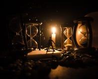tła pojęcia odosobniony przedmiota czas biel Sylwetka mężczyzna pozycja między hourglasses z dymem i światłami na ciemnym tle Zdjęcie Stock