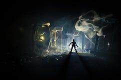 tła pojęcia odosobniony przedmiota czas biel Sylwetka mężczyzna pozycja między hourglasses z dymem i światłami na ciemnym tle Obraz Stock