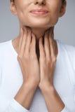 tła ręka odizolowywająca nad miejsca chorą bolesnego gardła białą kobietą Zbliżenie kobiety Piękne ręki I szyja Gardło ból Obrazy Stock