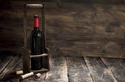 tła szkła czerwone wino Butelka czerwone wino na stojaku z corkscrew Fotografia Stock
