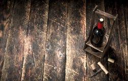 tła szkła czerwone wino Butelka czerwone wino na stojaku z corkscrew Zdjęcie Stock
