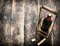 tła szkła czerwone wino Butelka czerwone wino na stojaku z corkscrew Fotografia Royalty Free