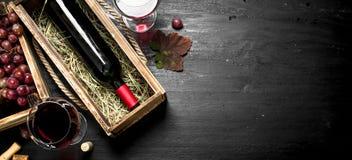tła szkła czerwone wino Czerwone wino w starym pudełku z corkscrew Zdjęcie Stock