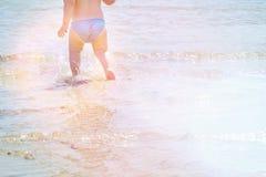 Tło błękitny morze z małymi dziecko nogami w wodzie Wakacje z dzieciakami plażowej brzegowej cibory śródziemnomorska piaska kamie Zdjęcie Royalty Free