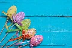 tło barwiący Easter jajek eps8 formata czerwony tulipanu wektor Stubarwni dekorujący Easter jajka, barwiący proszek na turkusowym Zdjęcie Royalty Free