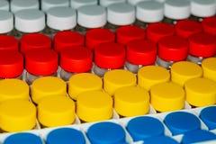 Tło białe, czerwone, żółte i błękitne puszki, zdjęcie stock