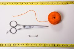 Tło dla krawieckiej pomarańczowej nici, pomiarowej taśmy i nożyc, zdjęcia stock