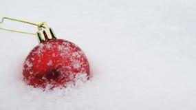 Tło dla nowego roku i bożych narodzeń, Bożenarodzeniowa piłka w śniegu Obraz Stock