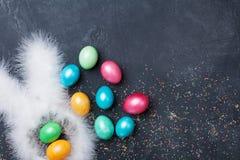 tło Easter śmieszny Confetti, królików ucho i kolorowi Wielkanocni jajka na czarnym stołowym odgórnym widoku, Odbitkowa przestrze Zdjęcie Stock