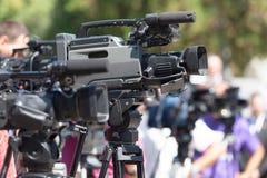 tło mikrofonów prasy konferencja odizolowane white Kamera telewizyjna w ostrości przeciw zamazanemu bac fotografia stock