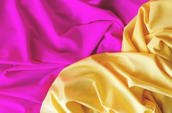 Tło od atłasowej tkaniny kolor żółty i menchie barwimy fotografia stock