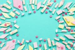 Tło, rama z marshmallows, cukierki i lizaki na turkus powierzchni, kopii przestrzeń, odgórny widok zdjęcie royalty free