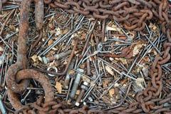 Tło starzy ośniedziali przegięci gwoździe, rygle, dokrętki, śruby, łańcuch Fotografia Royalty Free