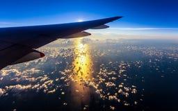 Tło wizerunek światło słoneczne nad oceanu i samolotu skrzydła widok obraz stock