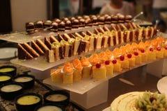Tło wypełniał z kolorowymi tortami i deserami z świeżymi owoc Obrazy Stock