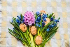 Tło z ciastkami w formie Wielkanocnych jajek w błękitnych śnieżyczkach na w kratkę kuchennym ręczniku Fotografia Stock
