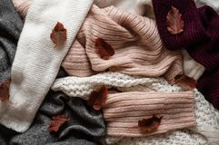 Tło z ciepłymi pulowerami Stos trykotowy odziewa z jesień liśćmi, przestrzeń dla teksta, jesieni zimy pojęcie kosmos kopii obrazy stock