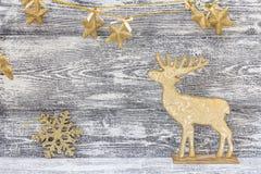 Tło z złotymi Bożenarodzeniowymi dekoracjami - renifer, snowfla Zdjęcie Stock