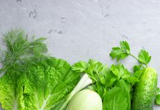 Tło z zielonymi warzywami, sałatką, ogórkiem, zieloną cebulą i zucchini na szarość kamienia stole, zdjęcie royalty free