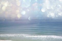 Tło zamazana plaża i morze macha z bokeh światłami, rocznika filtr Fotografia Stock