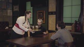 Tłuściuchna kelnerka przynosi zimnego piwo mężczyźni siedzi przy stołem w barze z pigtails w białym gorseciku i bluzce zdjęcie wideo