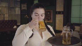 Tłuściuchna kelnerka z pigtails w białej bluzce kraść napój od klienta szkła Śmieszna dziewczyna no może opierać się i pić zbiory