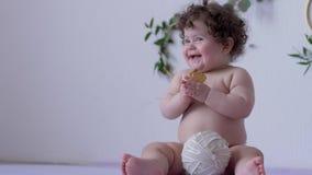 Tłuściuchny śmieszny dziecko z kędzierzawym włosy je ciastko obok piłki w studiu na tle ściana z wystrojem zbiory