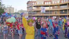Tłum dorosli i dzieci w kostiumach z flagami w rękach chodzimy wzdłuż miasto ulicy podczas świątecznego festiwalu zbiory wideo
