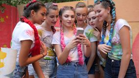 Tłum dziewczyny z jaskrawymi warkoczami z gadżetem w rękach na na wolnym powietrzu, Roześmiana drużyna młodość spojrzenia przy fo zbiory wideo
