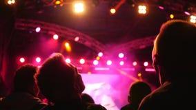 Tłum fan i falowanie głowa skacze przy festiwalem muzyka na żywo przy jaskrawym iluminującym floodlights zbiory wideo