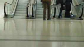 Tłum pasażery z bagażem i torba na zakupy dalej toczy wewnątrz pośpiech eskalator W obrazku może widzieć zdjęcie wideo