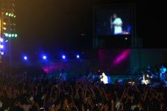 Tłum przy koncertowym festiwalem muzyki Szczęśliwi ludzie podnosi ręki up fotografia stock