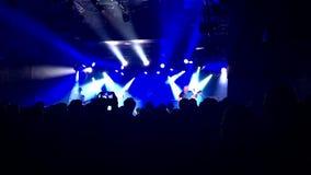 Tłum przy rockowym koncertem Sylwetka ludzie Światła i lasery, artyści na scenie zbiory wideo