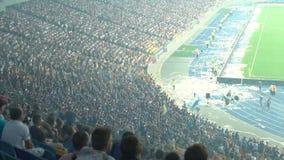 Tłum skanduje i skacze w stojakach fan, ludzie rozwesela dla drużyna narodowa. zbiory