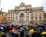 Tłum z wielo- kolorów parasolami jest trwanie pobliskim Trevi fontanną