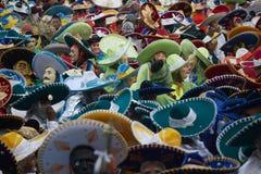 Tłum zamaskowani ludzie jest ubranym kolorowych charros kapelusze przy meksykańskim karnawałem zdjęcia stock