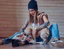 T恤杉和牛仔裤的一位时髦的tattoed白肤金发的女性坐与两条逗人喜爱的狗的一个木地板 免版税库存照片