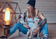 T恤杉和牛仔裤的一位时髦的tattoed白肤金发的女性坐与两条逗人喜爱的狗的一个木地板 免版税图库摄影