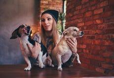 T恤杉和牛仔裤的一位时髦的tattoed白肤金发的女性拥抱两条逗人喜爱的狗 图库摄影