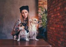 T恤杉和牛仔裤的一位时髦的tattoed白肤金发的女性拥抱两条逗人喜爱的狗 免版税图库摄影