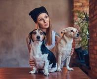 T恤杉和牛仔裤的一位时髦的tattoed白肤金发的女性拥抱两条逗人喜爱的狗 免版税库存图片