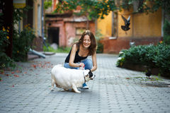 T恤杉和牛仔裤的一个快乐的女孩,抚摸一条肥胖狗,在t 免版税库存照片