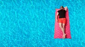 T恤杉的在可膨胀的床垫的人和短裤在游泳池 免版税库存照片